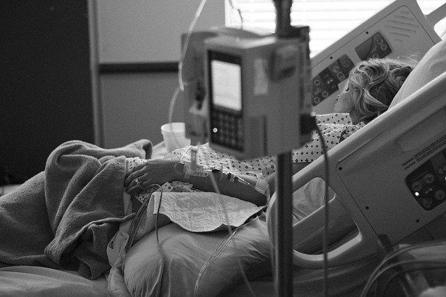 A woman in a hospital bed rests after a procedure, preparing for a long recovery